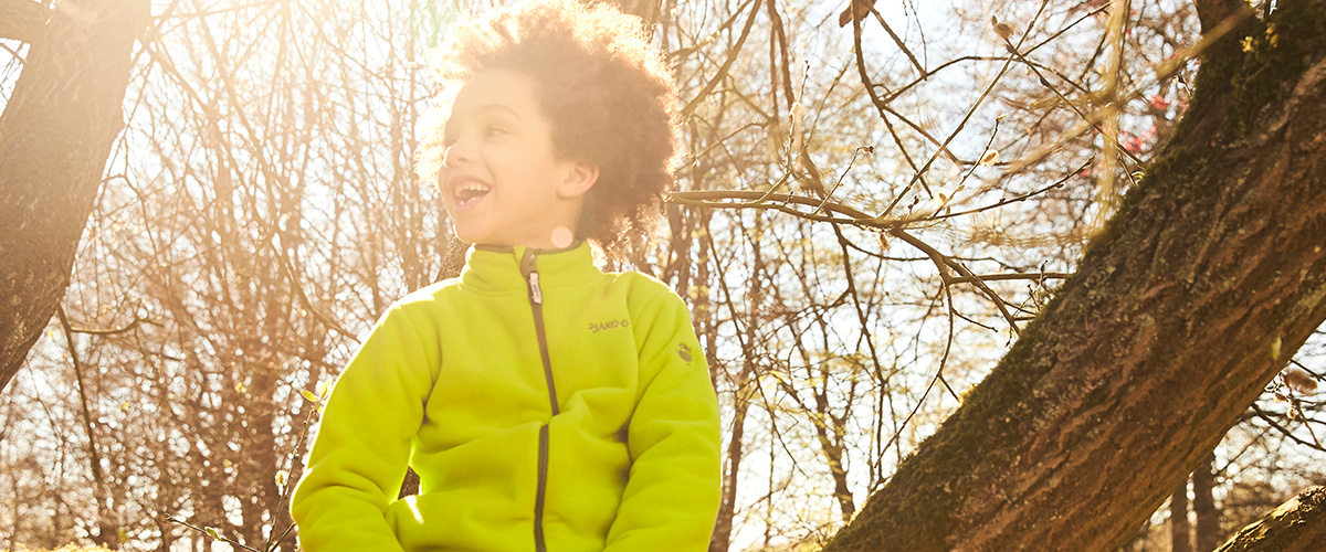 Junge klettert im Herbst auf einen Baum