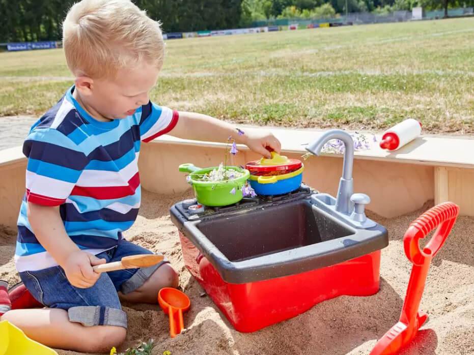 Kind spielt draußen im Sandkasten