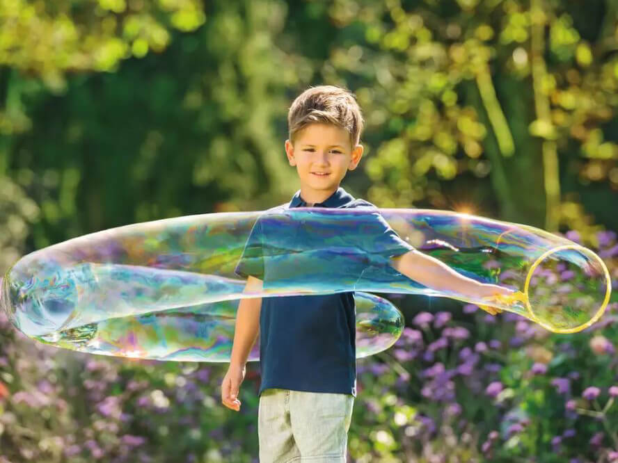 Kind macht draußen Seifenblasen