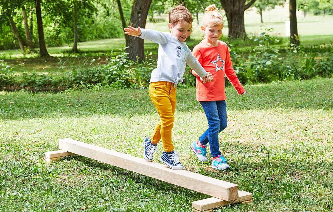 Bewegungsspiele: Kinder balancieren auf Balken