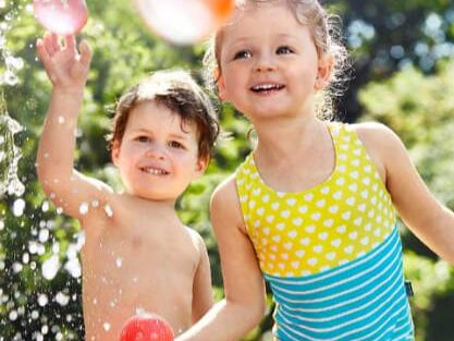Kinder spielen draußen mit Wasser